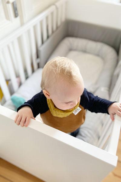 Baby Bente steht im Babybett Oscar von PAIDI.